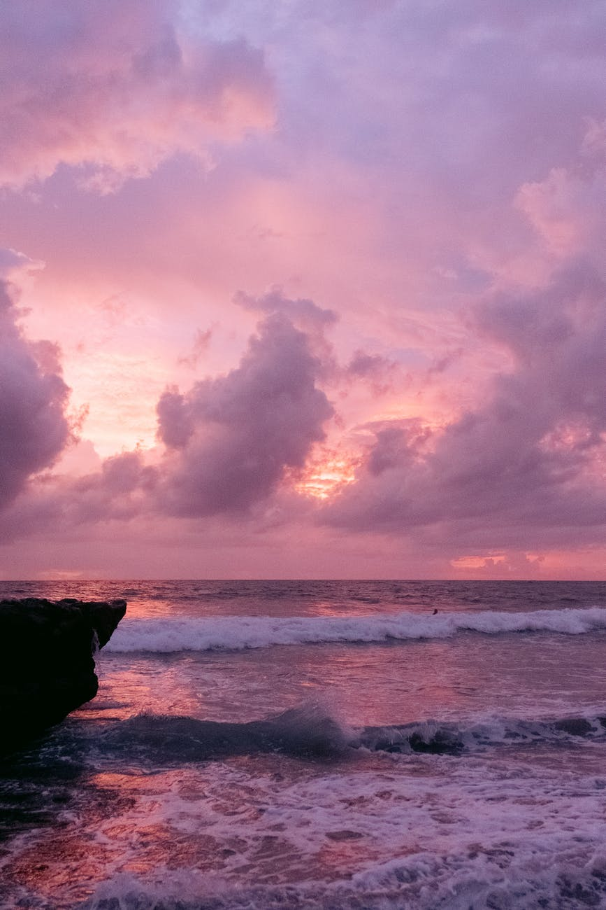 Waves gently crashing into the beach against a reddish purple sunset