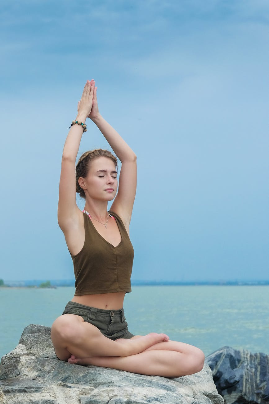 Lady sitting on a rock in front of blue sea and blue sky holding a yoga pose