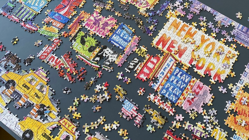 Jigsaw puzzle, half finished, colourful image of Times Square with yellow taxis in the foreground