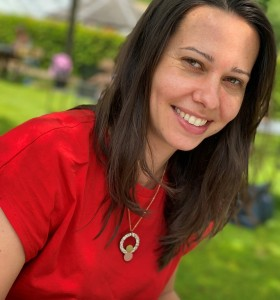 Women with shoulder length dark brown hair wearing a bright red t-shirt